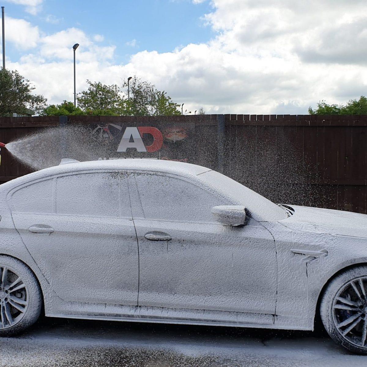 man coating car with snow foam