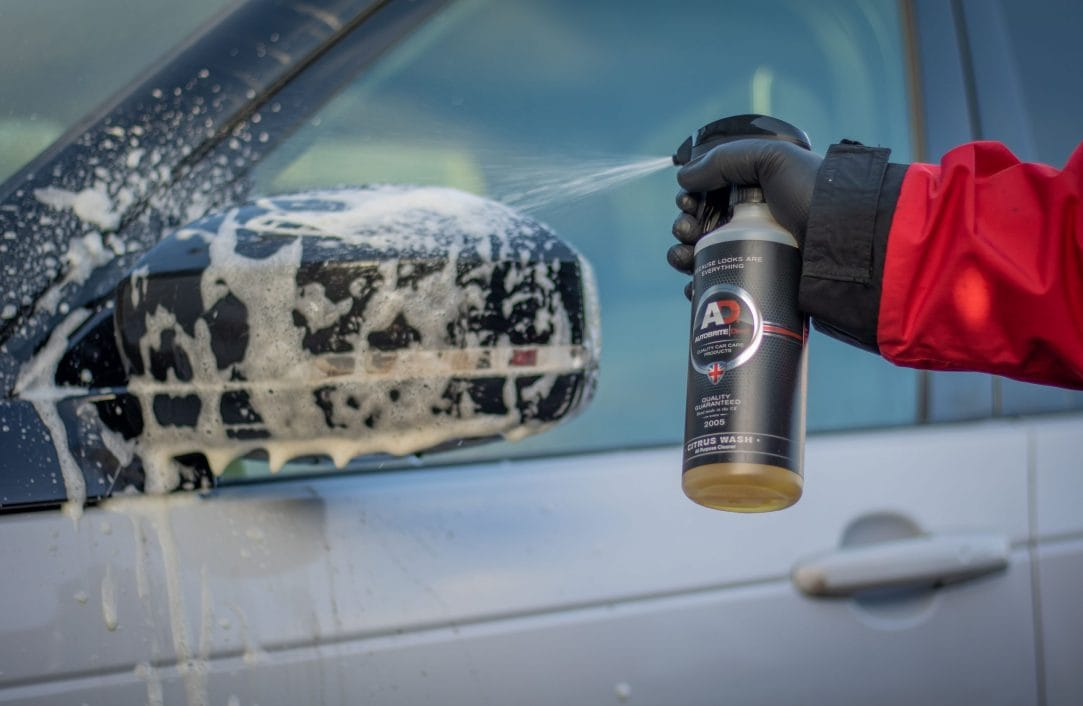 hand spraying citrus wash onto wing mirror